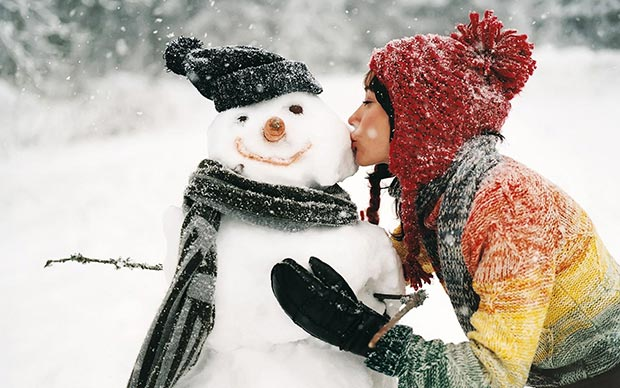 Girl kisses snowman