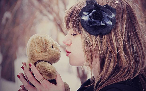 She kisses her teddy bear