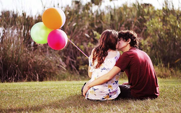 In-love couple kiss sitting on a lawn with balloons