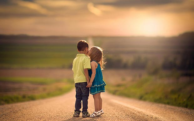 Children (kids) kiss on the road