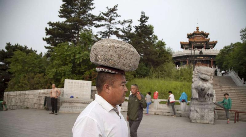 Chinese man carries 40 kg stone on his head to lose weight